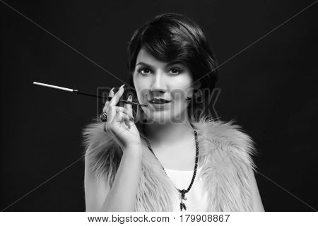 Young woman with cigarette holder on dark background