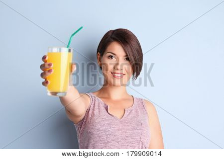 Young beautiful woman with glass of orange juice, on light background
