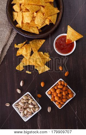 Nachos chips. Tortilla snack with sweet salsa or chilli sauce. Mexican salsa and pistachios nuts. Rustic plate on wooden background.
