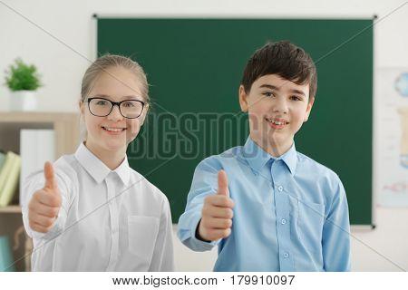 Cute boy and girl standing near green school blackboard in classroom