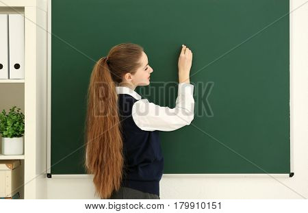 Beautiful long-haired schoolgirl writing at blackboard in classroom