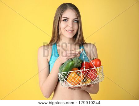Young beautiful woman holding basket with vegetables on yellow background
