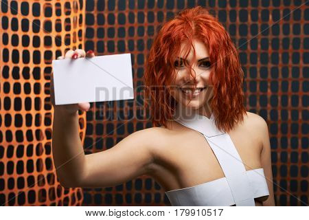 Recommend you this. Attractive futuristic female smiling cheerfully holding out copyspace card