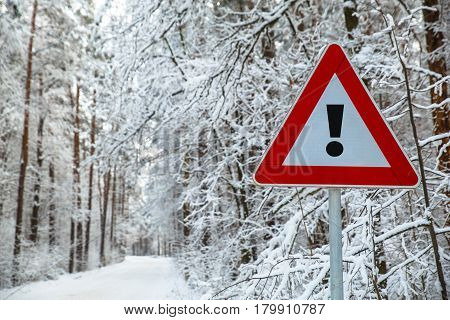 Snowy winter road. Exclamation mark. Attention sign. Forest with snow-covered trees. Beautiful wintertime.