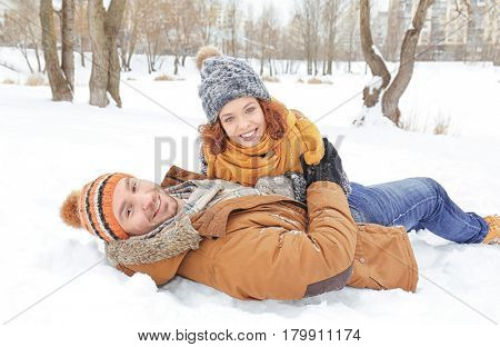 Lovely couple lying on snow in park