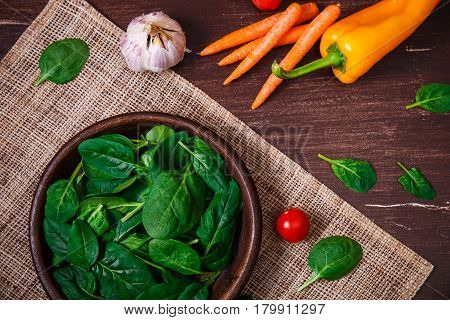 Spinach leaves in bowl. Carrot, pepper and cherry tomatoes. Garlic and brocoli. Raw fresh vegetable. Fresh natural plant leaf. Organic food on wooden table.