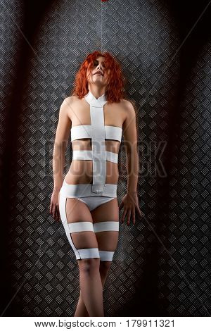 Lost in the world. Vertical shot of a stunning sexy futuristic woman wearing bandage outfit posing against metal wall