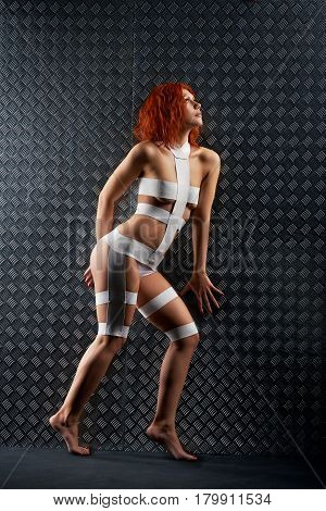 Gotta find the way. Full length Vertical soft focus portrait  of a gorgeous ginger hair female wearing bandage cosmic outfit slinking near the metal wall