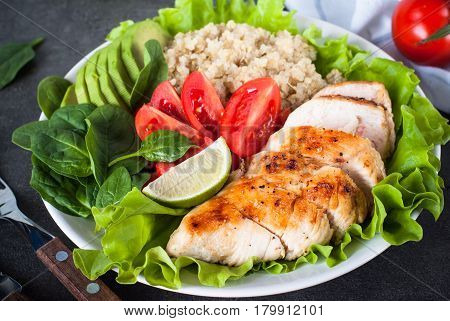 Balanced nutrition. Fresh salad from quinoa chicken breast avocado spinach lettuce and tomatoes. Healthy food. Portion plate.