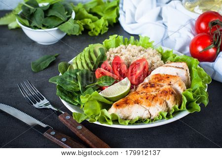 Balanced nutrition. Fresh salad from quinoa chicken breast spinach lettuce and tomatoes. Healthy food. Portion plate.