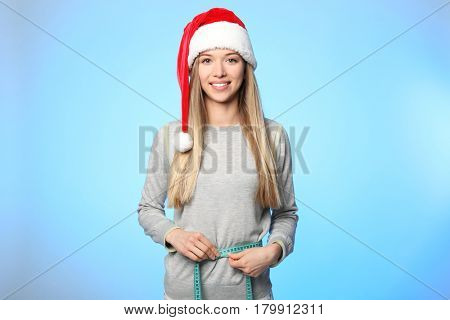Diet concept. Young beautiful woman with measuring tape on light background