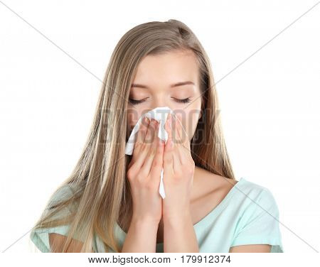 Young woman blowing nose on tissue against white background