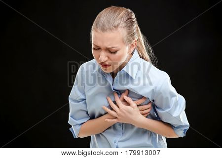 Heart attack concept. Young woman suffering from chest pain on black background
