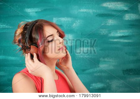 Young woman with colorful dyed hair listening to music on color background