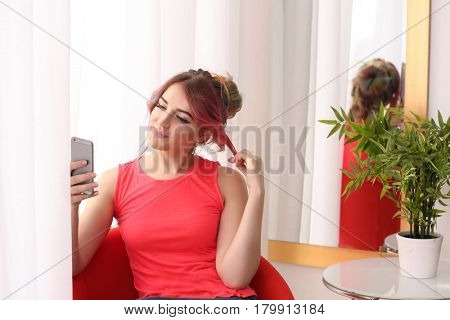 Young woman with colorful dyed hair sitting near window at home