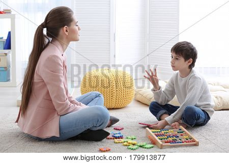 Cute little boy learning to count at private teacher's office