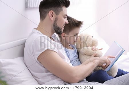 Dad and son reading interesting book while sitting on bed at home
