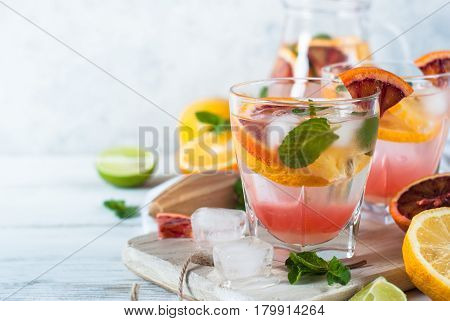Homemade lemonade in jug and glasses from different citrus. Refreshing summer drink with ice. Copy space.