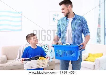 Dad and son with baskets of dirty clothes at home