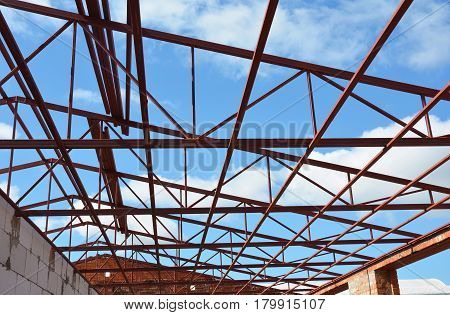 Roofing Construction. New Steel roof trusses details with clouds sky background. Industrial roofing.