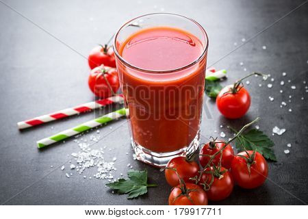 Fresh tomato juice and ingredients at dark slate table.