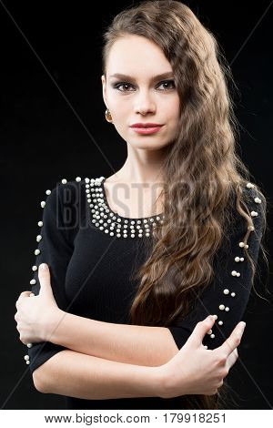 Beautiful woman with dark hair and evening makeup. Jewelry and Beauty. Fashion photo. Black background, sexy black dress