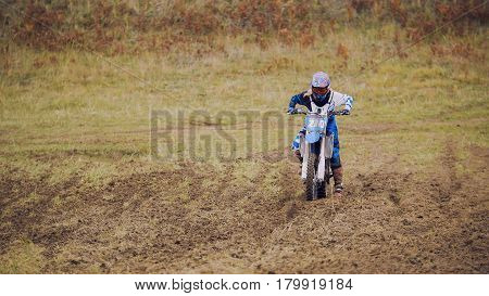 Crazy girl mx biker - motocross racer on dirt bike at sport track, telephoto