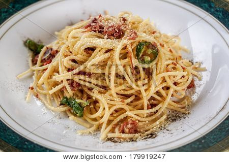 Traditional Italian Spaghetti aglio e olio with corned beef food background.The dish is made by lightly sauteeing minced or pressed garlic in olive oil, sometimes with the addition of dried red chili flakes, and tossing with spaghetti.