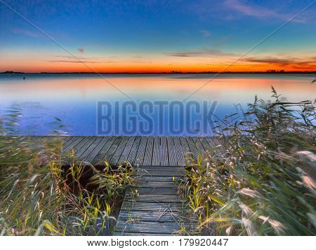 Long Exposure Image Of Blue And Orange Sunset Over Boardwalk On The Shore Of A Lake