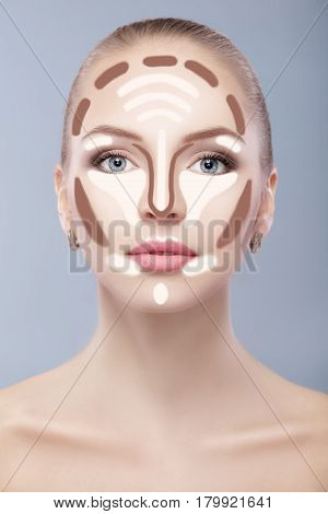 Contouring. Make up woman face on grey  background. Contour and highlight makeup. Professional face make-up sample