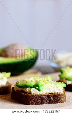 Hummus avocado sandwiches on a wooden board, avocado half, hummus in a glass bowl. Open sandwiches made with rye bread, avocado slices, hummus and roasted sesame seeds. Vertical photo