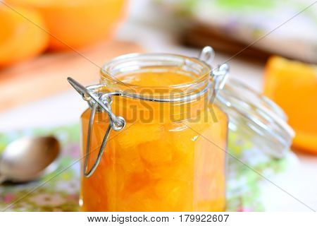 Home orange jam. Sweet orange jam in a glass jar, spoon, textile, napkin, orange slices on a table. Easy citrus dessert. Closeup