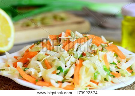 Coleslaw on a plate. Coleslaw salad with carrots, pumpkin seeds, greens and dressed with lemon juice and olive oil. Light and tasty diet salad. Closeup