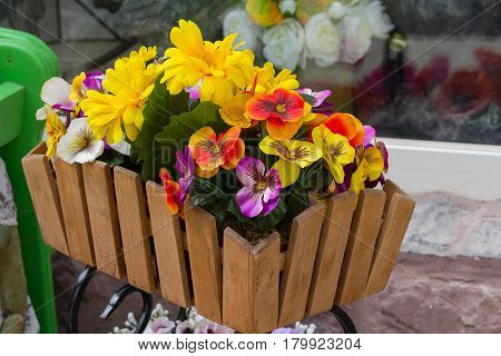 Artificial flowers in a wooden box on a city street