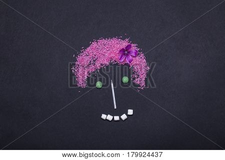 pink sprinkles sweets dragee marshmallow zephyr and birthday cake candle in shape of human girl face or smiley on grey background