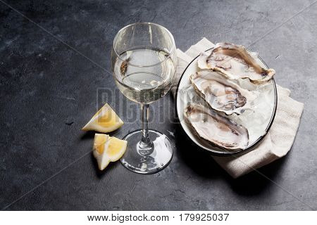 Opened oysters, ice and lemon and white wine on stone table. Selective focus on oysters
