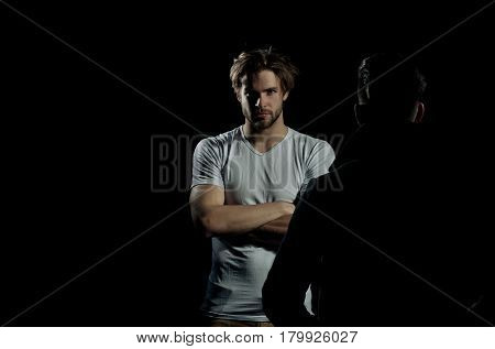 Two handsome men standing opposite on black background. Muscular macho unshaven caucasian in white tshirt with folded arms biceps triceps. Male businessman in dark coat copy space