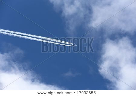 An airplane with four engines leaves an inverse trail on the cloudy sky