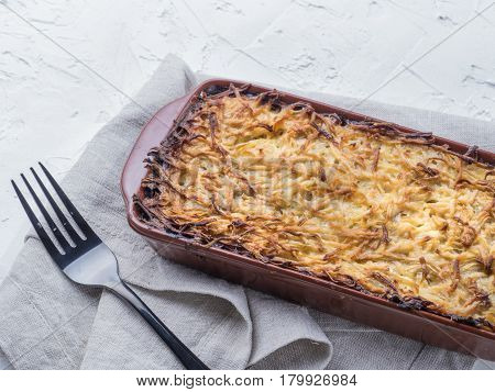 Close up view of appetizing potato casserole with fish, eggs and cream. Potato casserole in serving baking dish on white concrete background