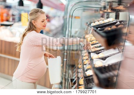 shopping, food, pregnancy and people concept - happy pregnant woman with paper bag and tongs buying buns at grocery store or supermarket