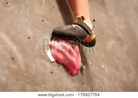 fitness, extreme sport, bouldering, people and equipment concept - foot of young woman in rock shoe on indoor climbing gym wall holds