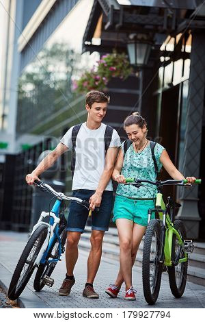 Young people, couple with bicycles on the street. A loving couple on a date on a summer evening. The guy with the girl hugs and kisses. Youth, first feelings, first love, first dates