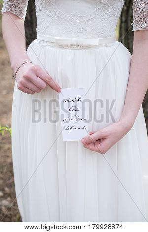 Bride holding a wedding card «Love always comes in time»