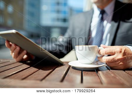 business, hot drinks, technology and people and concept - senior businessman with tablet pc computer drinking coffee from espresso cup outdoors