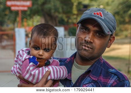 AGRA, INDIA - DECEMBER 2012: Indian family, father holding the daughter with black eyes in his lap