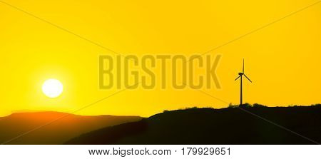 Silhoutte of a wind genator with yellow sky and sunset. Isle of Skye, Scotland.