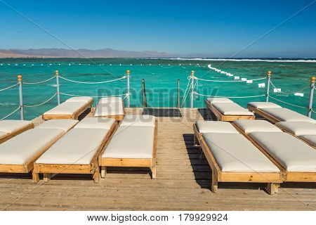 Pier with chaise longues in the sea in resort at sunset. Summer vacation. View at a clear sea with turquoise water. Summer vacation at a sea coastline in a exotic country.