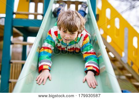 Happy blond kid boy having fun and sliding on outdoor playground. Funny joyful child smiling and climbing on slide. Summer, spring and autumn leisure for active kids. Boy in colorful fashion clothes