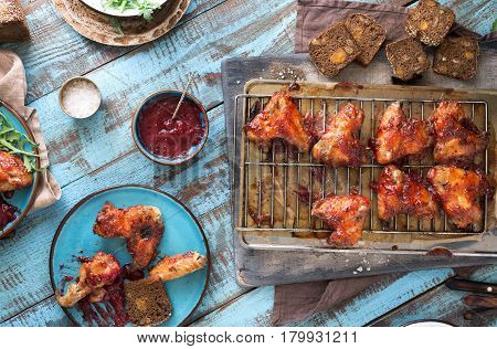 Chicken wings in cranberry sauce on wooden table top view. Homemade dinner party concept