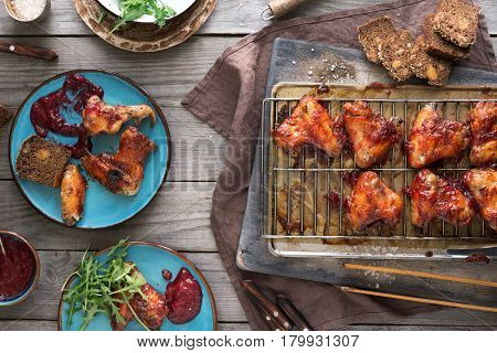 Top view dinner table with chicken wings in cranberry sauce. Top view rustic style. Dinner party food concept